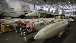 Två F/A-18C Hornet under däck på USS Carl Vinson, framför dem utrustning för elektronisk krigföring och extra bränsle