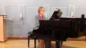 Kantor Eeva-Liisa Malmgren, dirigent för kören Kråksången, sitter och spelar på pianot i församlingsgården vid Esbo svenska församling.