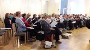 Kören Kråksången sitter och sjunger i Esbo församlingsgård.