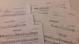 Närbild på notpapper till olika sånger som sjungs vid kören Kråksångens övning.