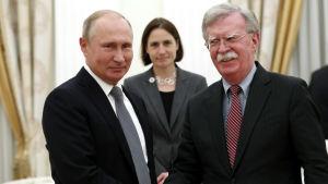 Vladimir Putin och John Bolton skakar hand, ler och tittar in i kameran.
