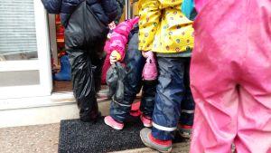 Daghemsbarn i regnkläder köar för att komma in till dagiset.