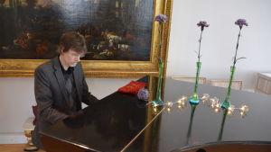 Rolf Danielsson spelar på Aktiastiftelsens flygel i stiftelsens representationsvåning.