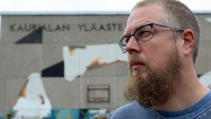 Kuvassa Tuomas Kyrö seisoo Kaurialan yläasteen edessä. Koulun nimi näkyy seinässä.
