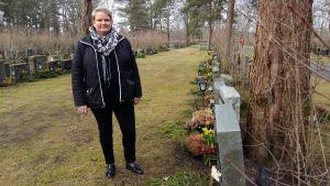 Byråchef Maria Wikström med en lutande gravsten, som har fått en gul lapp om att saken borde åtgärdas.