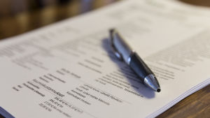 En penna på en fastighetsmäklares hög med papper, med uppgifter om en lägenhet som är till salu.