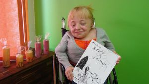 Monitaituri Noora Västinen istuu pyörätuolissaan. Hänellä on kädessään Roisku ja Loisku -lastenkirja, jonka hän on itse kirjoittanut ja kuvittanut.