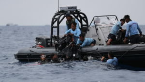 Indonesiska dykare arbetade vid olycksplatsen på tisdagen.