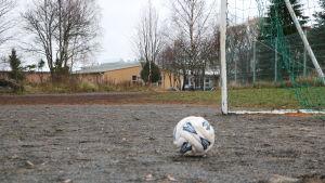 En fotboll ligger på en grusplan. I bakgrunden skymtar en skolbyggnad.