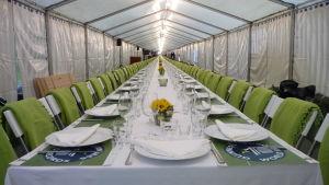 Bild på ett långt, dukat matbord inne i ett tält.