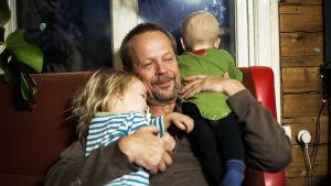 Mies istuu kaksi pientä lasta sylissään / olallaan.