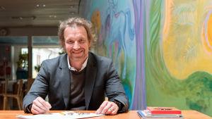 Kuvassa on Marco Mäkinen Helsingin Rudolg Steiner -koululla värikkään seinän vieressä pöydän ääressä.