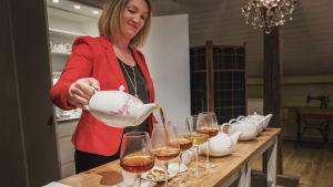 Anna Grotenfelt Paunonen kaataa teetä viinilaseihin teenmaistelu-tilaisuudessa.
