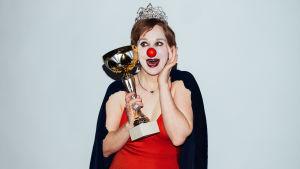 Babylon-klovni valitaan Miss Suomeksi. Klovni kruunu päässään ja valtikka kädessään.
