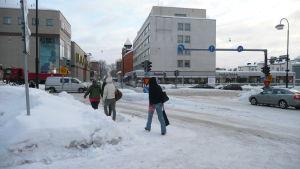 Flera personer går längs en gata i centrum av Borgå. Marken är täckt av snö.