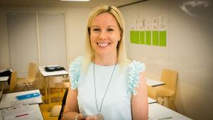 Vaaleahiuksinen opettaja hymyilee luokassa ja katsoo kameraan