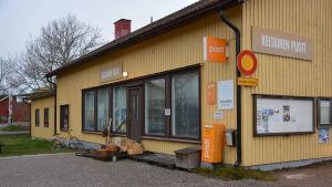 Ett gulmålat trähus i Gustavs med stora skyltfönster och postens logo utanpå.