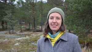 En leende Kaisa Kukkola med skog i bakgrunden.