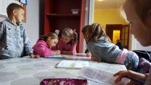 Barn läser läxor hos en hjälporganisation i östra Ukraina