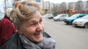 En leende pensionär i närbild med bilar i bakgrunden
