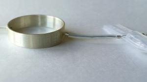 Närbild av silverringen i halsbandet Alliance.