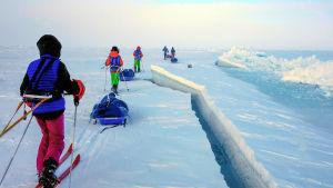 Viisi ihmistä hiihtää ahkiot perässään. Vieressä iso railo.