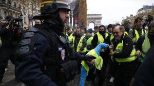 Polisen stoppar demonstranter på  Champs-Élysées på lördag förmiddag.