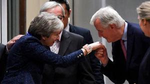 Jean Claude Juncker hälsar på Theresa May genom att kyssa hennes hand i Bryssel.