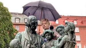 Skådespelare Oskar Pöysti bakom en Topeliusstaty