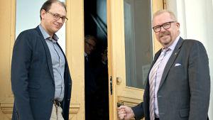 Två män i skjorta och kavaj, ena med slips, står på trappan till en gul stenbyggnad. Ena mannen håller dörren öppen för den andra. De ler och är på väg att stiga in i byggnaden.