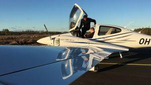 Ett litet flygplan i närbild. Två män är i cockpiten, en av dem håller på att hoppa ut.