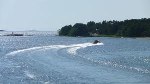 En båt svänger mot styrbord och ger vågor på en solglittrande fjärd.