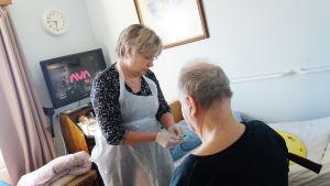 Kvinna iklädd plastförkläde hjälper äldre man som sitter ner. Kvinnan har en spruta i handen.
