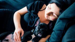 Nainen nukkuu koiran kanssa sohvalla.