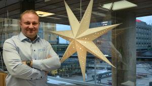 Max Jansson, vd för Visit Vasa står bredvid en julstjärna på sitt kontor i Vasa centrum.