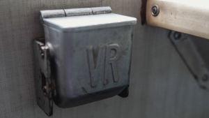 """Metallinen, vanhan junavaunun seinään kiinnitetty tuhkakuppi tekstillä """"VR""""."""