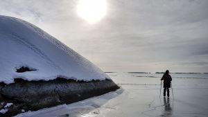 En skridskoåkare står på isen i skärgården, silhuett i motljus.