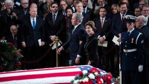 George Bush, med fru Laura, går förbi sin fars kista, draperad i USAs flagga.