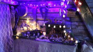 En julkrubba med en massa små figuriner står på ett bord. På väggen hänger lysande stjärnor.