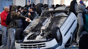 En demonstrant häller tändvätska på en bil som välts omkull i samband med lördagens demonstrationer i Marseille.