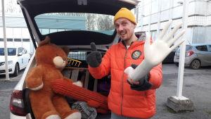 Jonathan Granbacka håller i en handen av en skyltdocka framför en fullpackad bil.