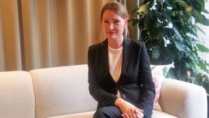 Charlotta Kvarnström sitter i soffa.
