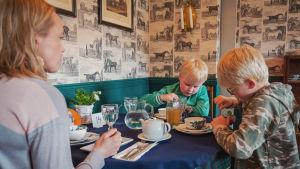 Asiakkaita pöydän ääressä teehuoneella Wehmaan kartanolla Juvalla.