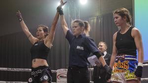Katarina Perkkiö (keskellä) tuomaroi thainyrkkeilyottelua ja nostaa voittajan käden ylös.