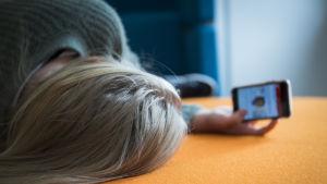 En flicka ligger på en soffa och granskar sin telefon.