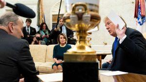 Trump håller upp anteckkningar om murens fördelar, Pelosi och Schumer tveksamma, i bakgrunden journalister.