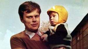 Kirjailija Tommi Kinnunen pikkupoikana isänsä sylissä