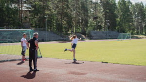 Nainen heittää saapasta urheilukentällä, kaksi miestä katsoo vieressä.