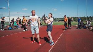 Nainen ja mies poseeraavat liitosaappaat kädessään, taustalla kilpailut käynnissä urheilukentällä.