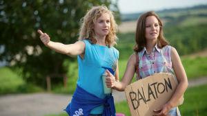Kaksi nuorta tyttö liftaamassa, kädessä kyltti Balaton